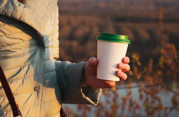Dziewczyna trzyma w ręku papierowy kubek na kawę. wolne miejsce na tekst