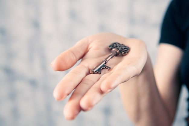 Dziewczyna trzyma w ręku stary klucz