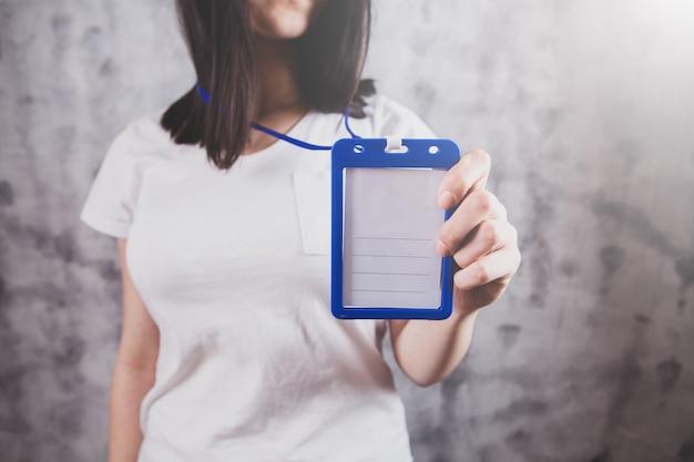 Dziewczyna trzyma w ręku znaczek z imieniem, makieta odznaki