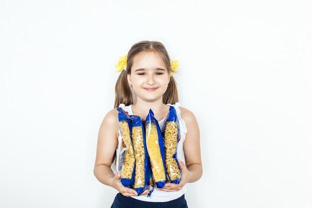 Dziewczyna trzyma w wiązkach makaron, spaghetti, ravioli, produkty z ciasta, wywar