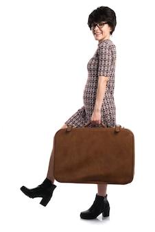 Dziewczyna trzyma walizkę z rocznika spojrzeniem