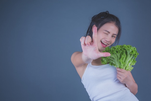 Dziewczyna trzyma warzywa na szarym tle.