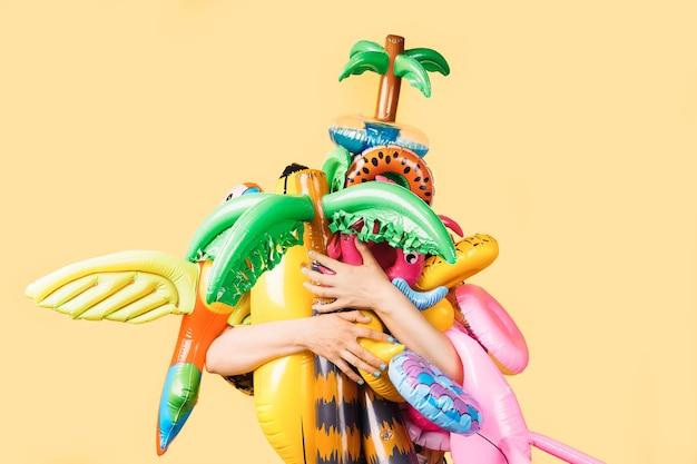 Dziewczyna trzyma wiele kolorowych pontonów basenowych na żółtym tle
