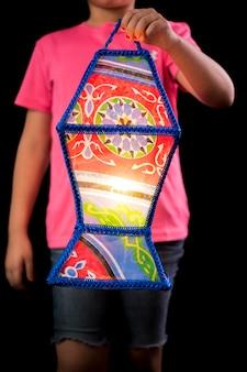 Dziewczyna trzyma wielką świąteczną latarnię ramadan