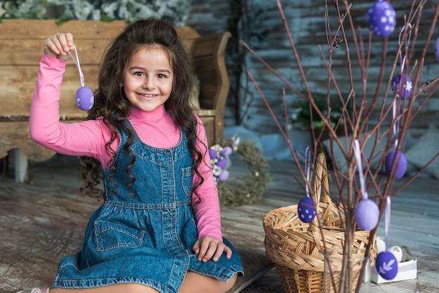 Dziewczyna trzyma wielkanocnego jajka blisko rozgałęzia się w wazie