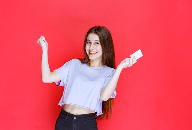 Dziewczyna Trzyma Wizytówkę I Pokazuje Pozytywny Znak Ręką. Darmowe Zdjęcia