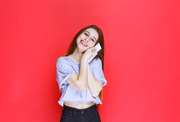 Dziewczyna trzyma wizytówkę i uśmiechnięty.