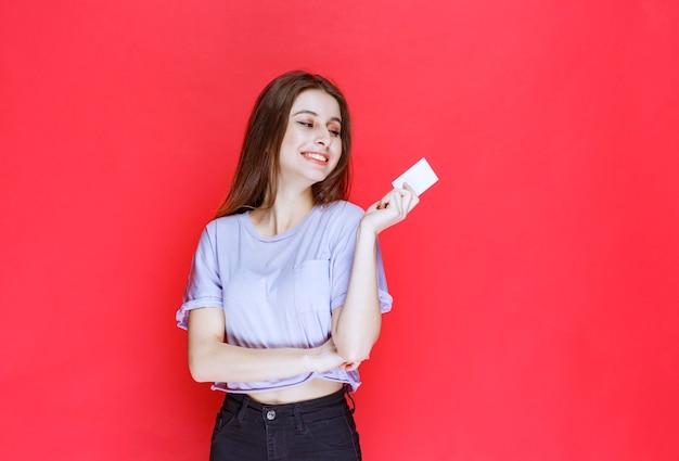 Dziewczyna trzyma wizytówkę i wygląda na szczęśliwą.