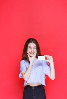 Dziewczyna trzyma wizytówkę i wygląda na zdziwioną i podekscytowaną.