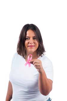 Dziewczyna trzyma wstążkę raka piersi na białym tle uśmiecha się.