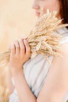 Dziewczyna trzyma złoty kłos pszenicy na polu pszenicy. kobieta trzyma pszenicę obiema rękami.