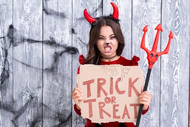 Dziewczyna trzyma znak cukierek albo psikus i trójząb