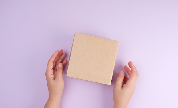Dziewczyna trzymać brązowe kwadratowe pudełko