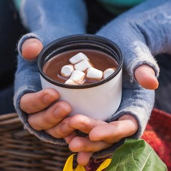 Dziewczyna trzymając się za ręce kubek gorącej czekolady lub kakao z bagiennym