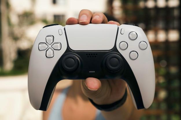 Dziewczyna trzymająca biały kontroler do gier nowej generacji.