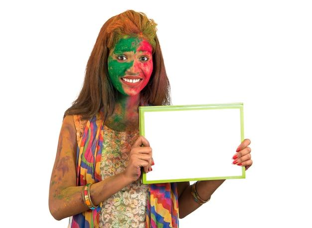 Dziewczyna trzymająca biały szyld z twarzą pomalowaną na kolor w festival of colour holi. na białym tle portret