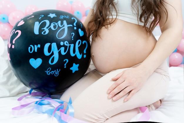Dziewczyna trzymająca czarny balon z chłopcem lub dziewczyną na płci ujawnia imprezę