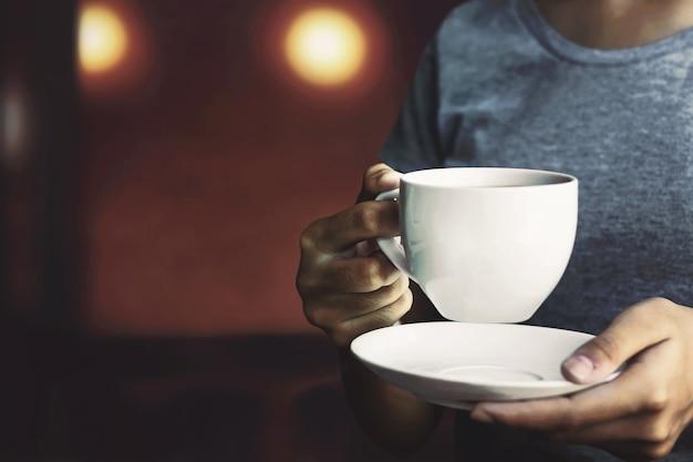 Dziewczyna trzymająca filiżankę gorącej kawy pijąca kawę rano