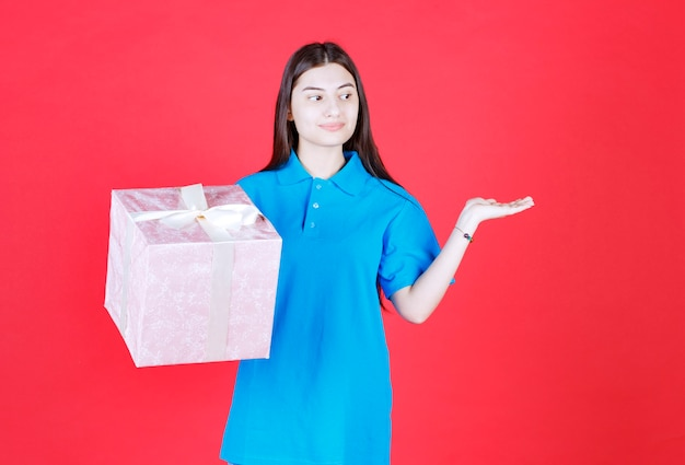 Dziewczyna trzymająca fioletowe pudełko upominkowe owinięte białą wstążką i zapraszająca kogoś do wręczenia prezentu