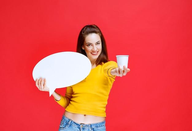 Dziewczyna trzymająca jednorazowy kubek napoju i owalną tablicę informacyjną i oferująca napój klientom.