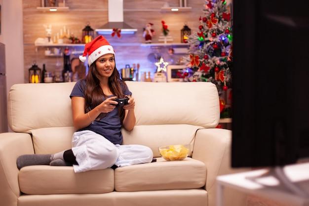 Dziewczyna trzymająca joystick do gier, grająca w gry wideo online podczas wirtualnej rywalizacji