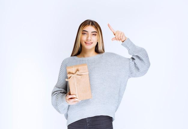 Dziewczyna trzymająca kartonowe pudełko i wskazująca na bok odbiornik.