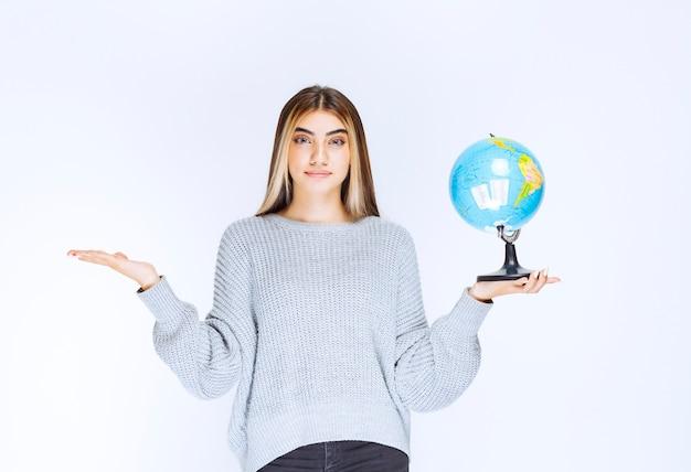 Dziewczyna trzymająca kulę ziemską i promująca ją.