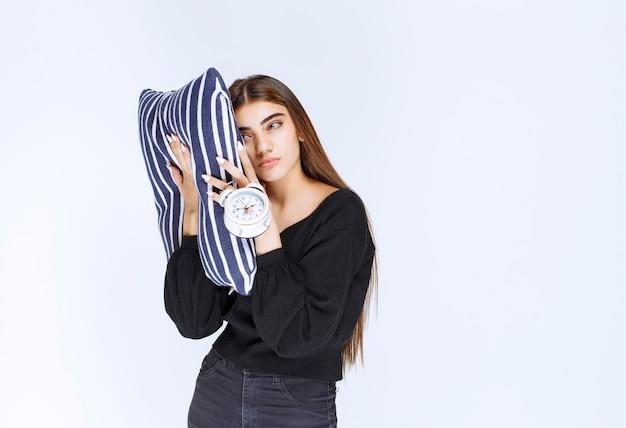 Dziewczyna trzymająca pasiastą poduszkę i pokazująca budzik ze smutną miną.