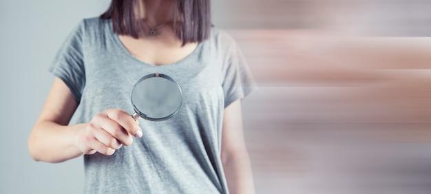 Dziewczyna trzymająca przed sobą lupę