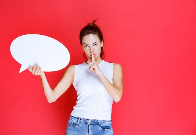 Dziewczyna trzymająca pustą owalną tablicę z pomysłami do gier i proszącą o ciszę.