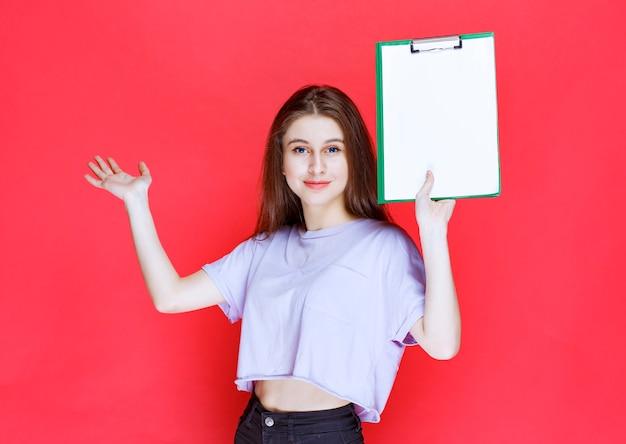 Dziewczyna trzymająca pusty arkusz sprawozdawczy i wskazująca na swojego kolegę.