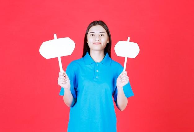 Dziewczyna trzymająca w obu rękach dwie tablice informacyjne