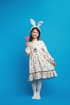 Dziewczyna trzymająca w rękach ciastko w kształcie serca na białym tle nad niebieską ścianą