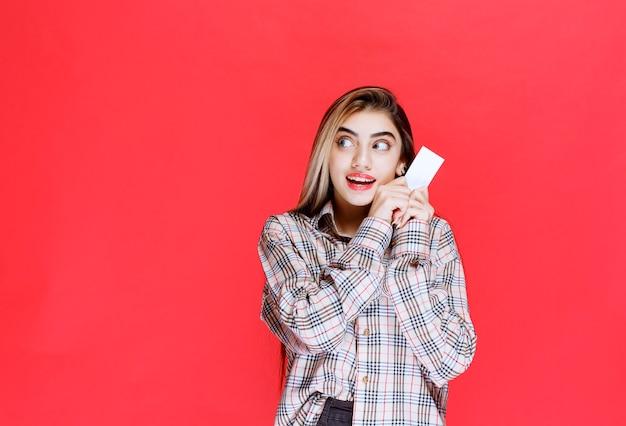 Dziewczyna trzymająca wizytówkę i coraz bardziej zdziwiona.