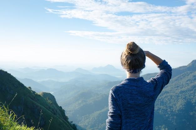 Dziewczyna turysta na szczycie góry w promieniach świtu, sri lanka