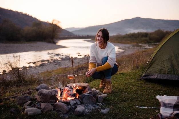 Dziewczyna turysta przygotowuje kiełbaski przy ognisku obok zielonego namiotu