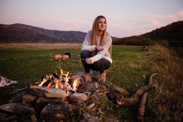 Dziewczyna turysta przygotowuje kiełbaski przy ognisku