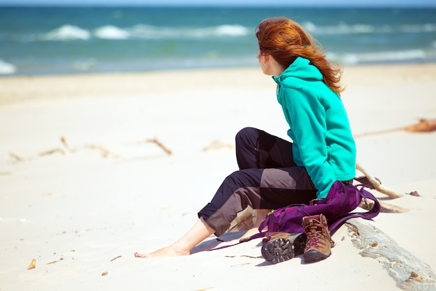 Dziewczyna turysta z plecakiem siedząca na plaży i patrząca na morze, morze bałtyckie