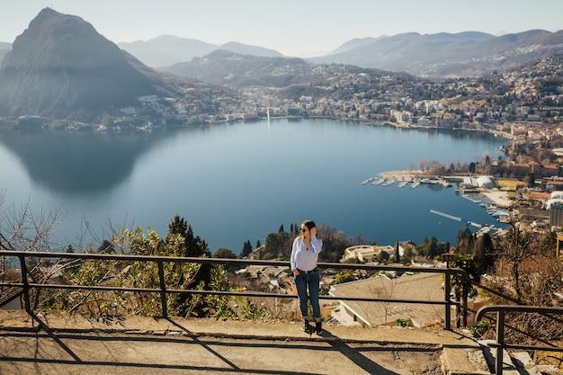 Dziewczyna turystyczny nad jeziorem lugano w szwajcarii patrząc na panoramę.