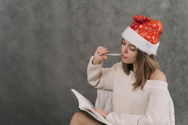 Dziewczyna tworzy listę życzeń na nowy rok. lista prezentów dla przyjaciół. dziewczyna w świątecznym kapeluszu pisze w zeszycie.