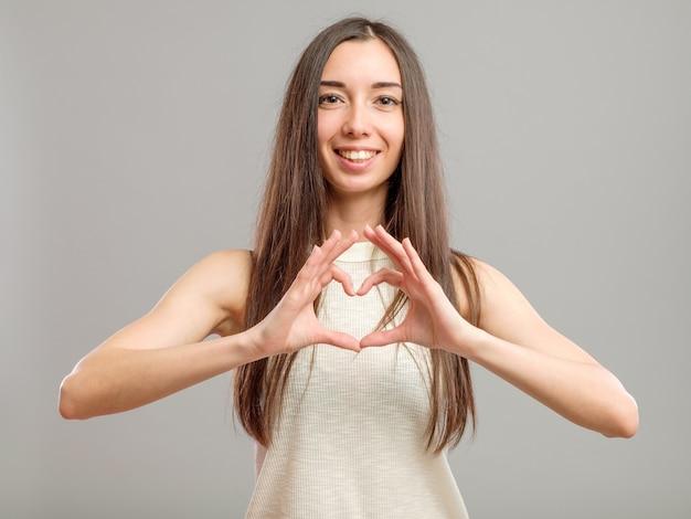 Dziewczyna tworzy serce z jej rękami