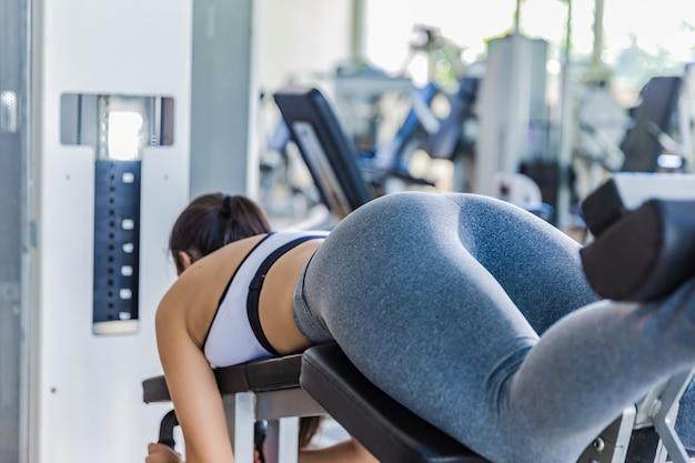 Dziewczyna tyłek z bliska. dziewczyna robi ćwiczenia na symulatorze na siłowni