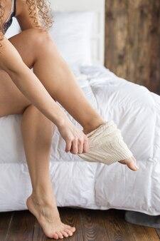 Dziewczyna ubiera podkolanówki siedząc na łóżku w sypialni.