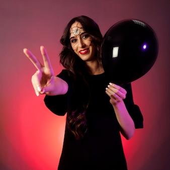 Dziewczyna ubrana jak czarownica czyniąc gest pokoju