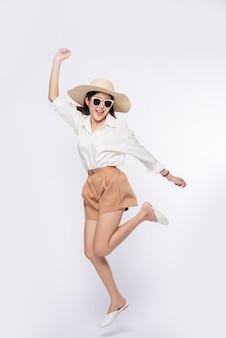 Dziewczyna ubrana w białą koszulę i szorty w kapeluszu noś okulary i uchwyt na kapeluszu
