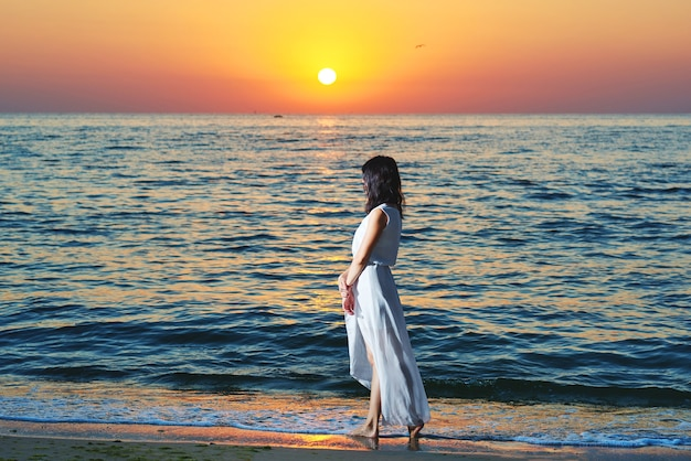 Dziewczyna ubrana w białą letnią sukienkę stojącą na piękny zachód słońca