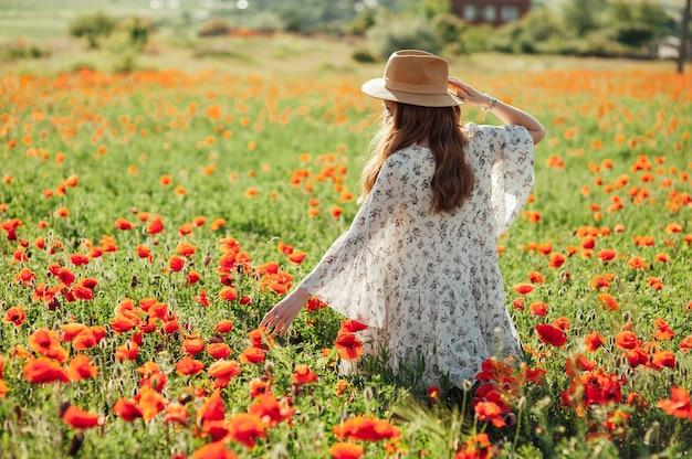 Dziewczyna ubrana w białą sukienkę i słomkowy kapelusz spaceruje wśród czerwonych kwiatów maku o zachodzie słońca. młoda kobieta cieszy się dobrą pogodą i zabawą na polu pełnym czerwonych kwiatów. koncepcja wiosny i natury