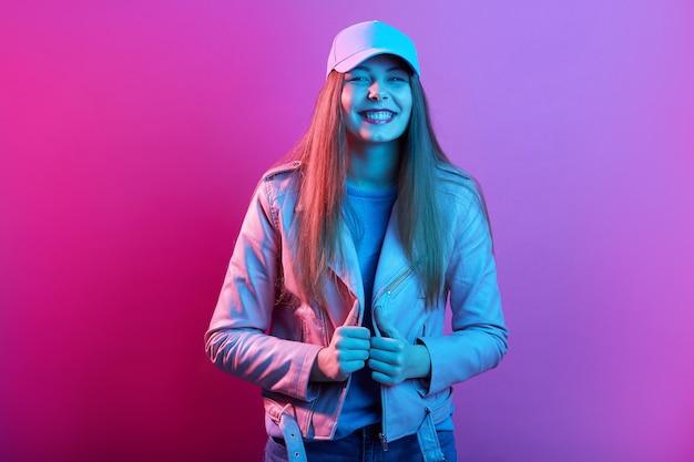 Dziewczyna ubrana w czapkę i skórzaną kurtkę z rękami na suwak patrząc uśmiechając się bezpośrednio do kamery, pozowanie na białym tle nad różową neonową przestrzenią