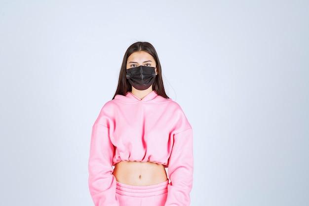 Dziewczyna ubrana w czarną maskę i czująca się bezpiecznie.