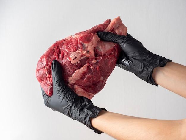 Dziewczyna ubrana w czarne rękawiczki trzymająca duży kawałek świeżej surowej wołowiny na jasnym tle